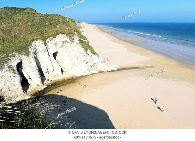 Couple walking on deserted beach at the White Rocks between Portrush and Bushmills, Northern Ireland  Eroded limestone cliffs