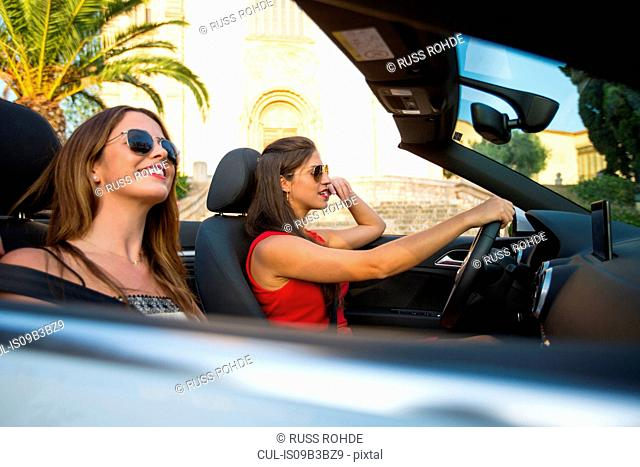Two young women tourists driving convertible, Calvia, Majorca, Spain