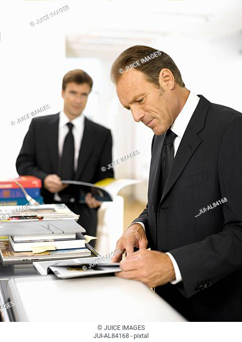 Businessmen looking at paperwork in office