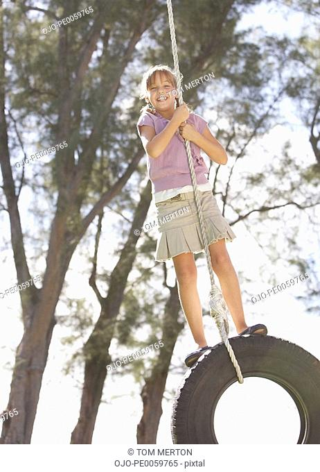 Young girl outdoors at park playing on tire swing