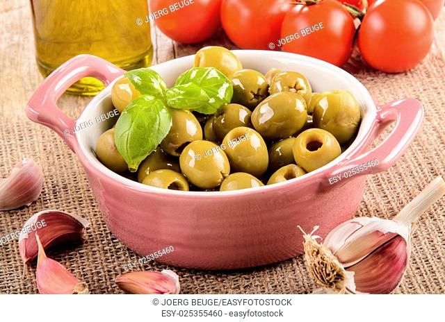 green olive in a pink bowl, garlic, tomatoes and olive oil in a glass bottle on jute