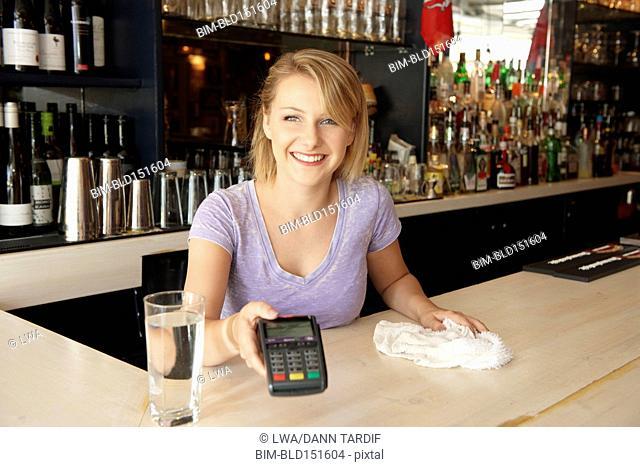 Caucasian bartender holding credit card reader in bar