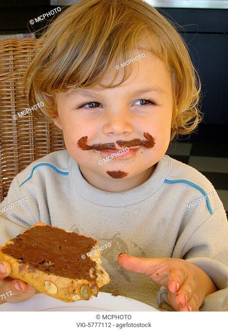Ein keiner Junge isst ein Nutella-Broetchen und hat einen Schoko-Bart, 2006 - Germany, 12/10/2006