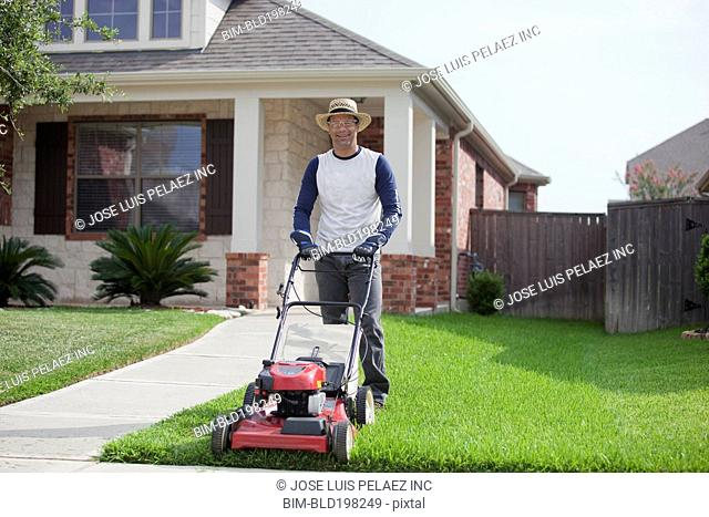 Hispanic man mowing his lawn