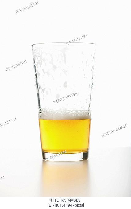 Studio shot of half full beer glass
