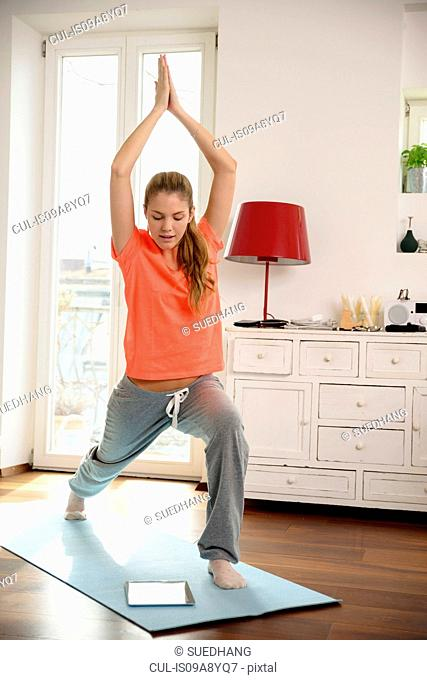 Young woman using digital tablet to aid exercise