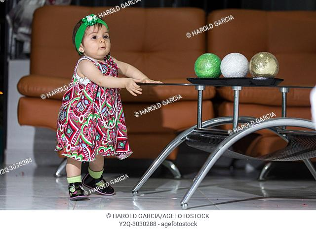 Girl playing with colorful balls in a living room