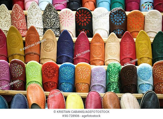 A stack filled with colorful baboushes - the traditional leather slippers of Morocco in the souq in the heart of the medina of Fès el-Bali, Fès, Morocoo