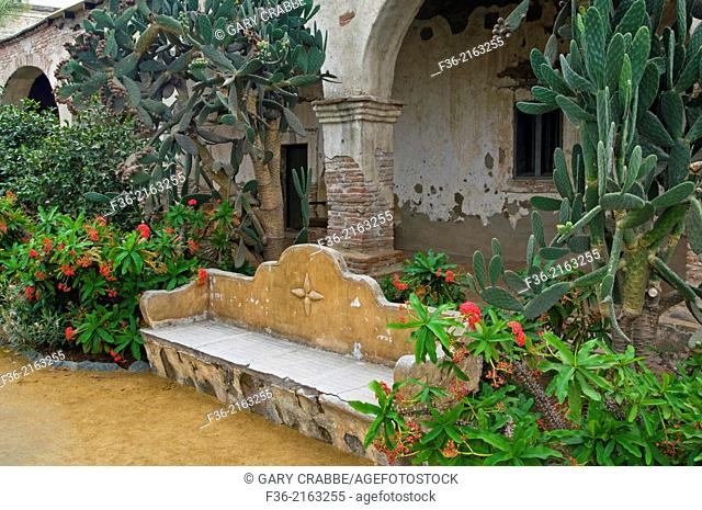 Garden bench and old stone walls at Mission San Juan Capistrano, San Juan Capistrano, California