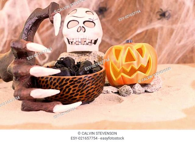 Halloween witch hand reaching for a bowl of rats