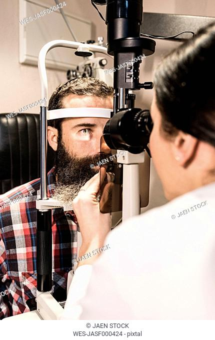 Optometrist examining eyes of a bearded man
