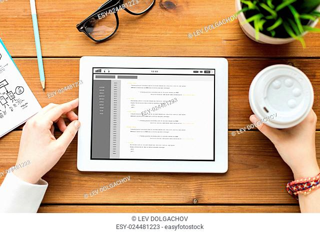 business, education, technology, people and programming concept - close up of woman with coding on tablet pc computer screen and coffee on wooden table