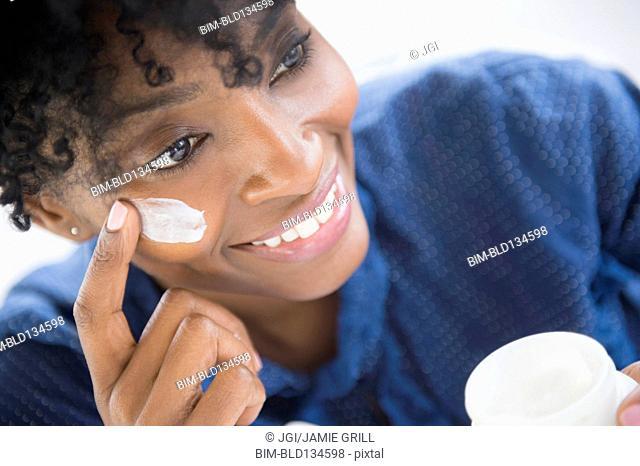 Black woman applying lotion to her cheek