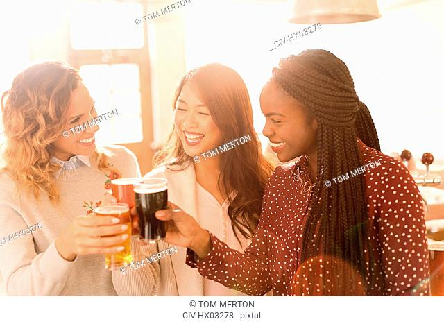 Women friends toasting beer glasses in bar