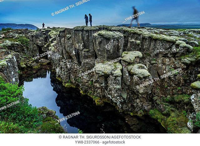 People standing by Flosagja fissure, Thingvellir National Park, Iceland