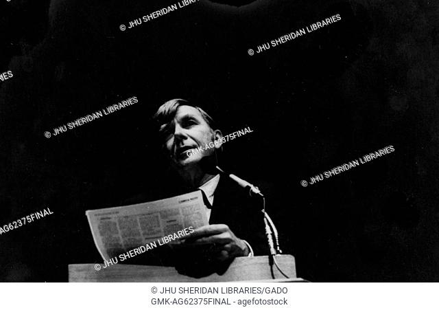 Russell Baker, Candid photograph, Shoulders up, Three-quarter view, Speaking at podium, c 60 years of age, 1965