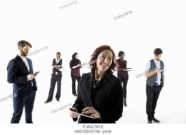 Business people using cell phones, digital tablets and laptop against white background