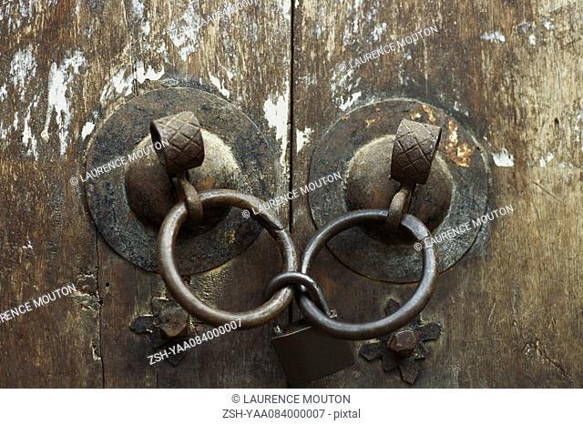 Old wooden doors, close-up of iron door handles linked by padlock
