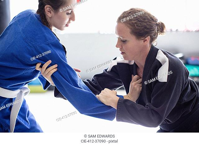 Focused women practicing judo in gym