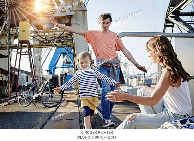Germany, Hamburg, father and daughter balancing on rail at the harbor