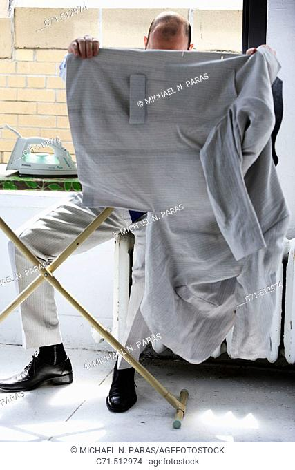 Man sitiing on radiator ironing clothes and hiding face with jacket
