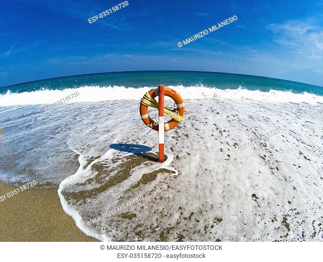 The waves reach the lifebelt in the deserted beach, even the sea is deserted