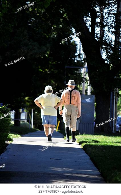 An elderly couple walking on a shady sidewalk under green trees, Ontario, Canada It's their daily routine - alone, when one is sick