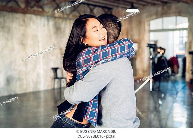 Couple hugging in open plan studio