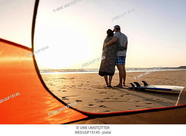Romantic couple camping on the beach, embracing at sunset