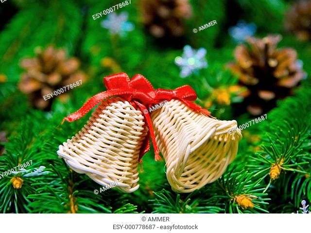 Two straw christmas bells, decorations on christmas tree branches, background
