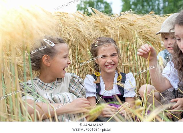 Germany, Saxony, children sitting in a grain field having fun