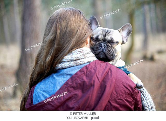 Portrait of cute dog being carried through forest by young woman