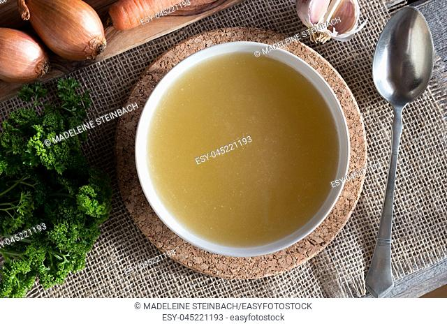 Chicken bone broth served in a soup bowl, with onions, carrots, parsley and garlic in the background, top view