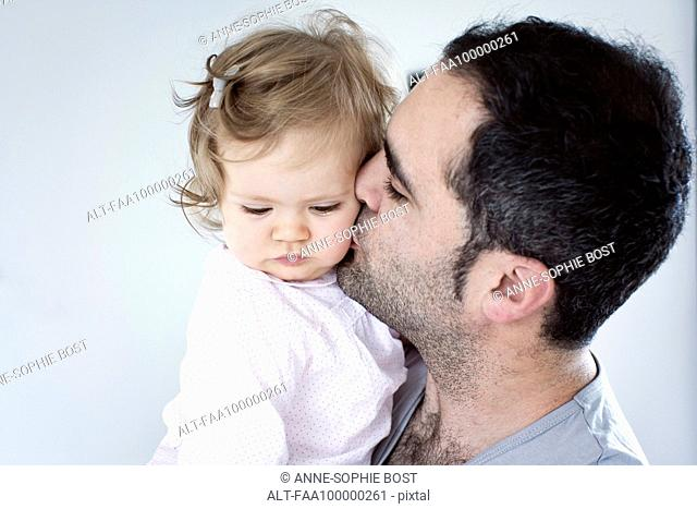 Father kissing baby girl's cheek