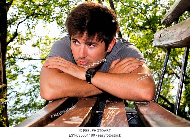 handsome young man leaning on a bench in the park