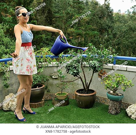 Young woman with sunglasses posing while watering the plants