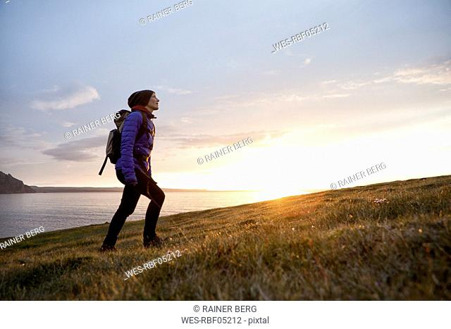 Iceland, woman hiking at twilight upon a hill