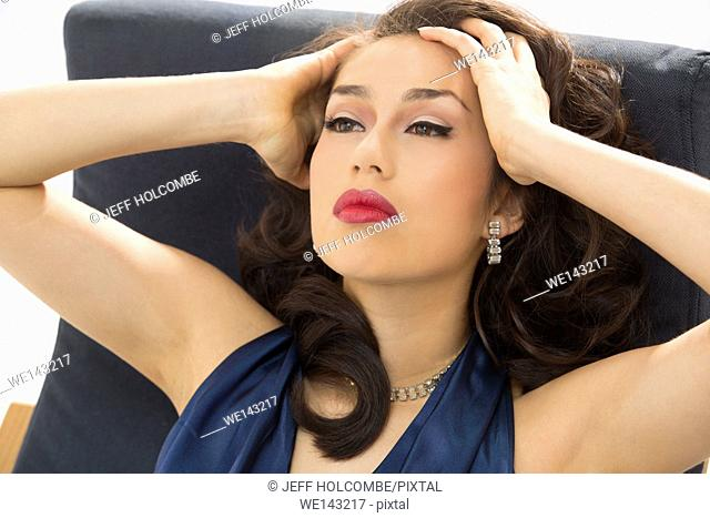 Beautiful young woman head and shoulders portrait, in vintage blue dress, sitting in a blue chair looking away, hands on temples
