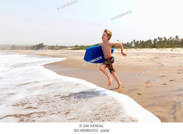 Boy running on beach, Goa, India, Asia