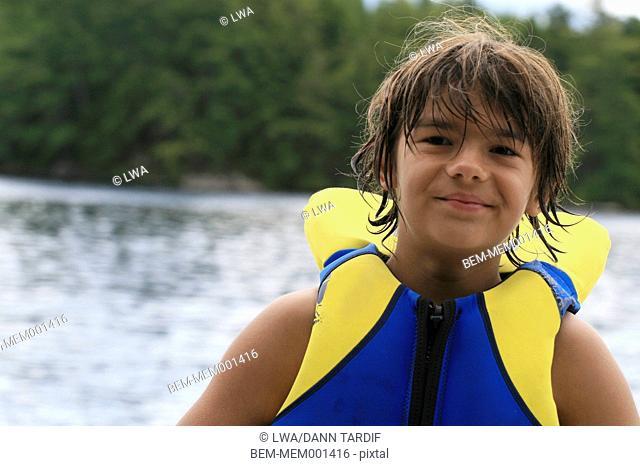 Caucasian boy wearing life jacket on lake