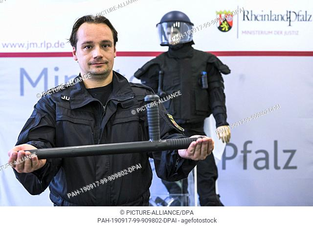 16 September 2019, Rhineland-Palatinate, Mainz: At a press conference at the Ministry of Justice, John Klein, prison officer, holds the new baton in his hands