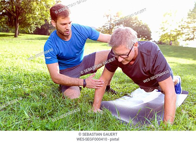 Man doing pushups on a meadow while his personal trainer watching him