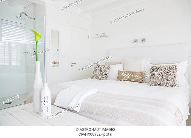 White bedroom with en suite shower in luxury hotel room