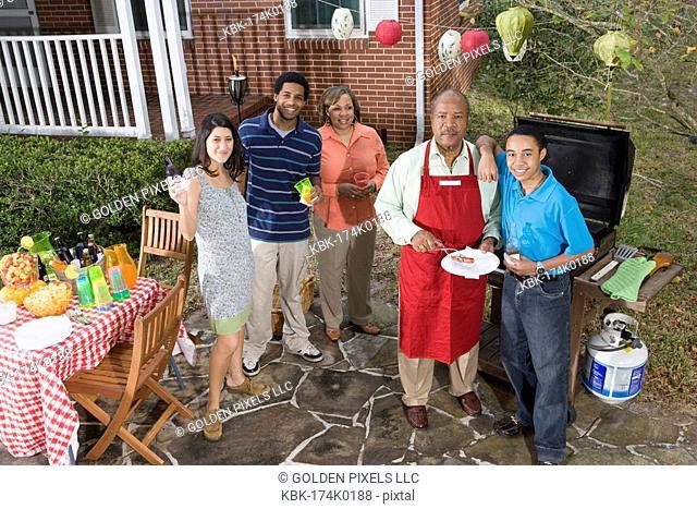 Family and friends enjoying backyard cookout