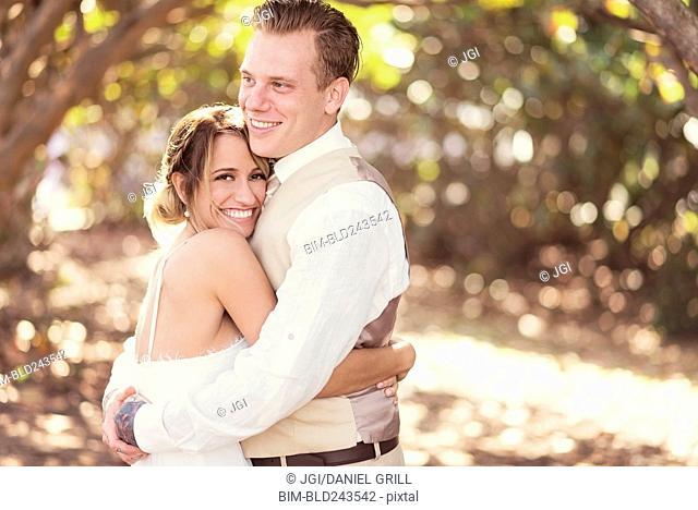 Caucasian bride and groom hugging outdoors