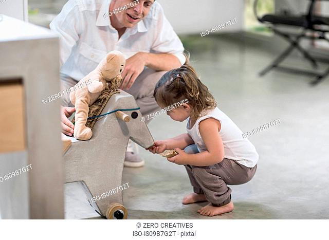 Father and baby girl looking at rocking horse