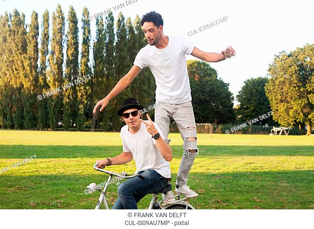 Two male friends fooling around on bicycle in park