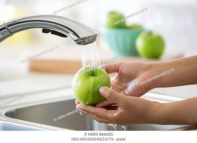 Womans hands rinsing green apple under kitchen faucet