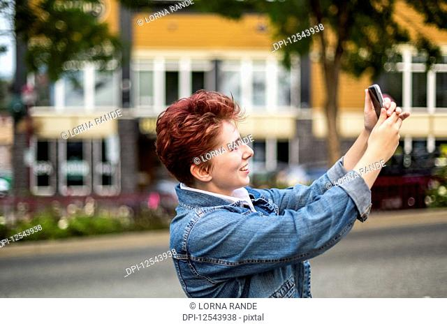 A teenage girl with red hair taking a self-portrait with a smart phone; Abbotsford, British Columbia, Canada