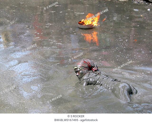 Voodoo follower in in mud with fire in Plaine du Nord, Haiti, Plaine du Nord